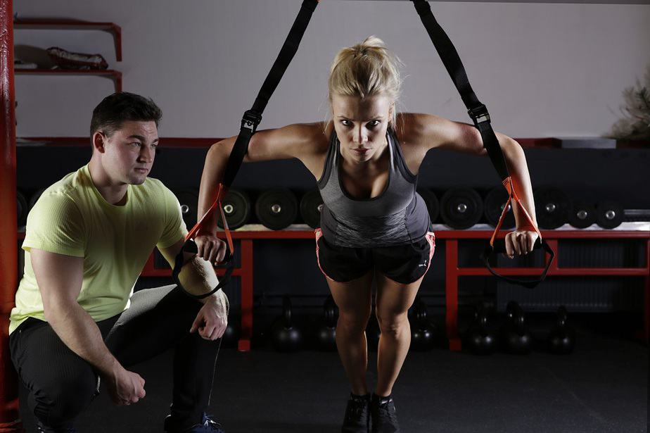 a young woman exercising with a trainer