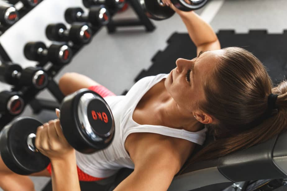 7 Health And Fitness Goals To Achieve Before 2021 Ends - a girl has a training with dumbbells.