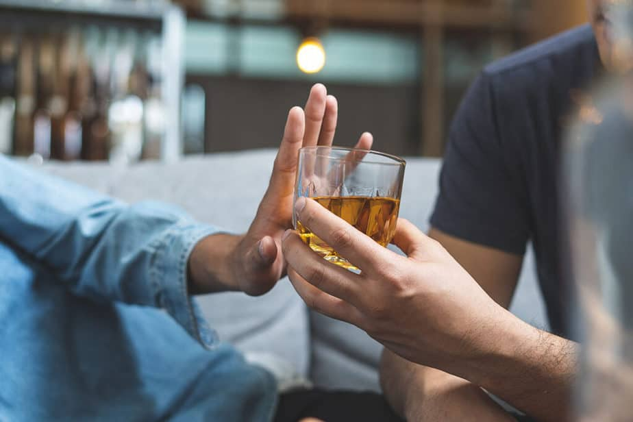 7 Health And Fitness Goals To Achieve Before 2021 Ends - A man is refusing a bad habit (alcohol).