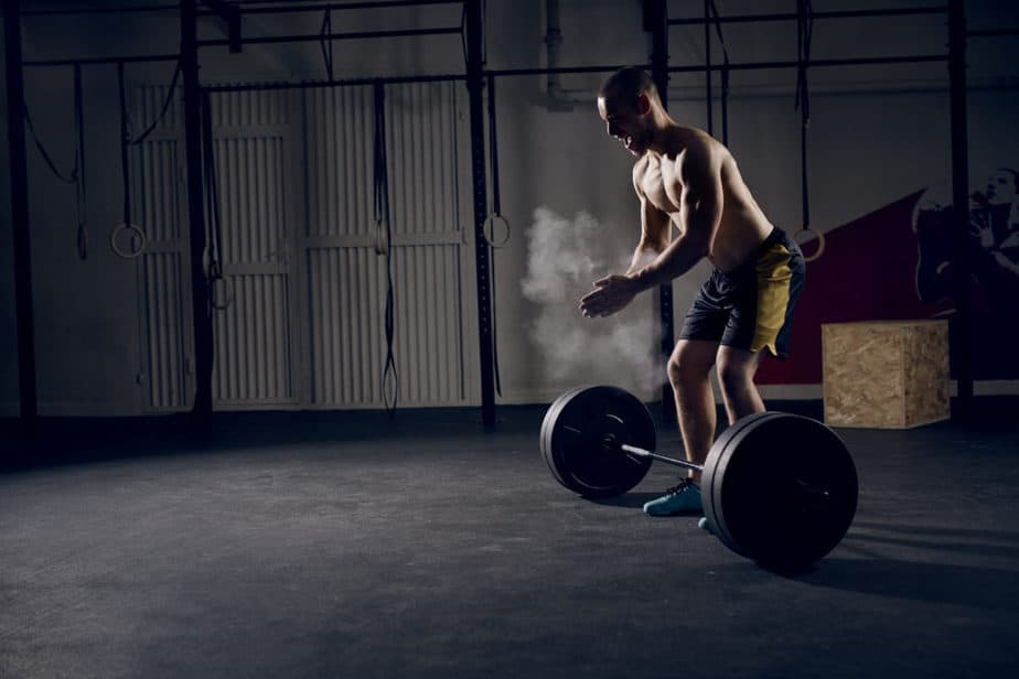 How to Increase Muscle Strength in the Fastest Way - A guy is preparing for weightlifting at the gym.