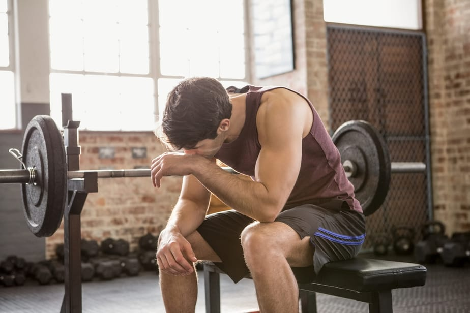 How to Increase Muscle Strength in the Fastest Way - A guy is resting after weightlifting.